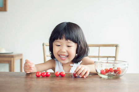 only 3 people: Girl with bowl of cherries LANG_EVOIMAGES