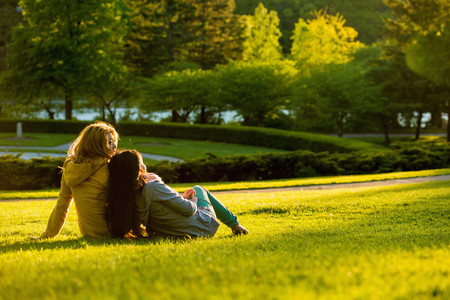 leaning against: Two young women relaxing in park