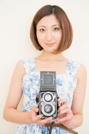 Smiling woman holding a 1960s classic camera