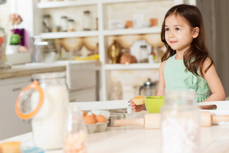 front house: Young girl at kitchen counter measuring ingredients