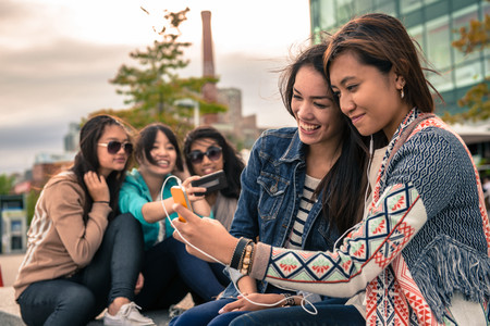 Young women taking self portrait photographs using smartphones