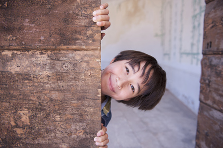 peep: Portrait of boy peeking from behind wood