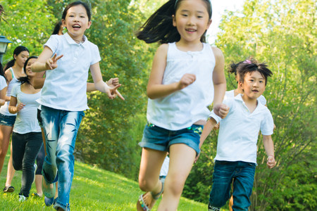 preadolescent: Boys and girls running in park