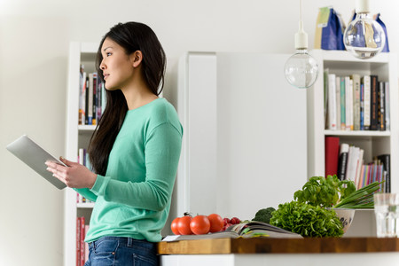kitchen cabinets: Profile of woman holding digital tablet leaning against table