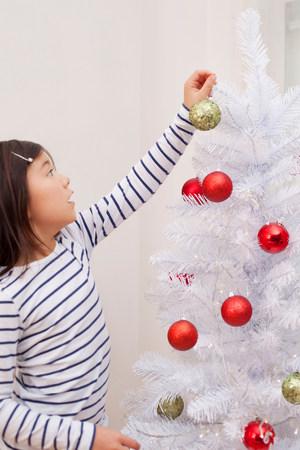 decorating: Girl decorating Christmas tree