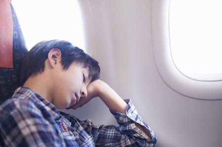 checker: Boy asleep on aeroplane LANG_EVOIMAGES