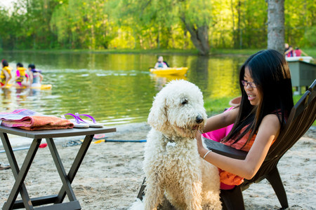 Girl sitting on chair by lake with dog
