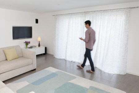 Man with mobile phone walking past curtains