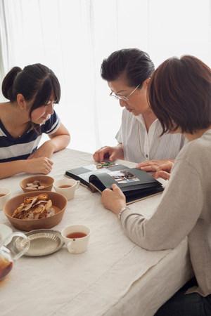 photo album: Three generation family looking at photograph album