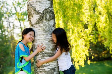 preadolescent: Two girls hugging tree