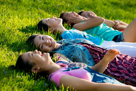 Girls lying on grass LANG_EVOIMAGES
