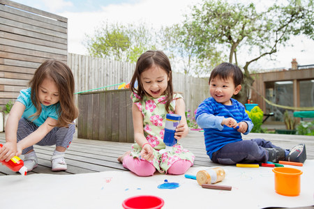 front house: Three young children painting and drawing in garden LANG_EVOIMAGES