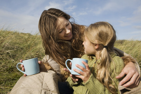 Mother and daughter outdoors with drinks