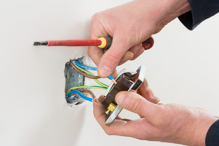 to mend: An electrician fixing a socket