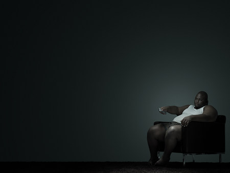 Overweight man watching television LANG_EVOIMAGES