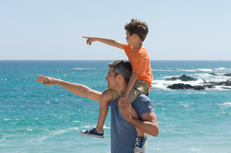 indicate: Father and son pointing at the sea