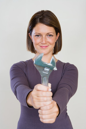 looking at viewer: Portrait of a woman holding a spanner