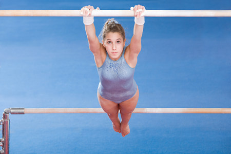 Gymnast hanging on uneven parallel bars LANG_EVOIMAGES