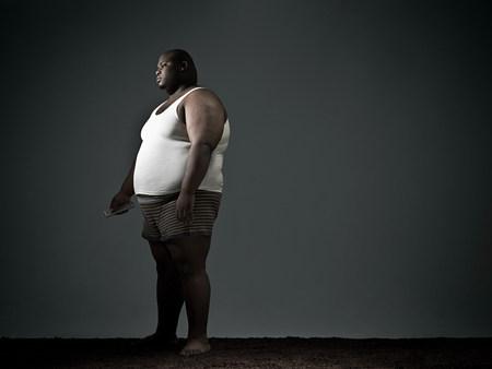 unhealthiness: Overweight man in underwear watching tv