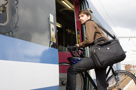 northern european: Man with bike getting onto train LANG_EVOIMAGES