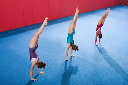 Gymnasts in a row doing handstands LANG_EVOIMAGES