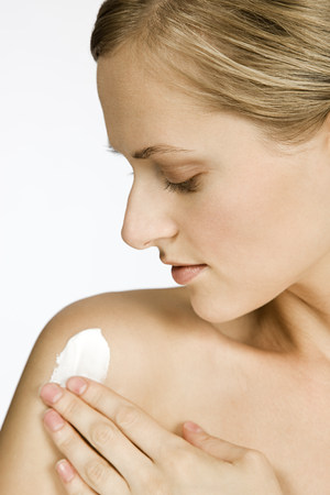 Woman applying body lotion LANG_EVOIMAGES