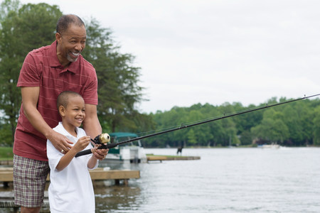 A grandfather teaching his grandson to fish LANG_EVOIMAGES