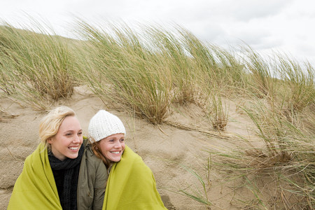 Women sharing a blanket on dune LANG_EVOIMAGES