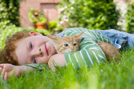 looking at viewer: A boy holding a kitten LANG_EVOIMAGES