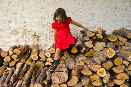 age 5: A girl climbing on logs
