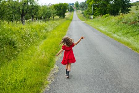 saltar: Una niña saltando por un camino rural