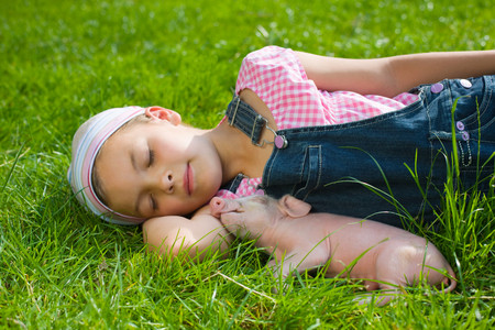 A girl and a piglet sleeping