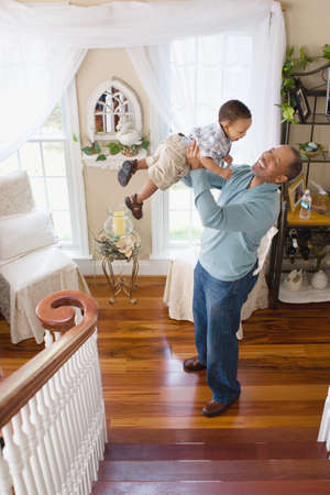 afro caribbean ethnicity: A grandfather lifting his grandson in the air