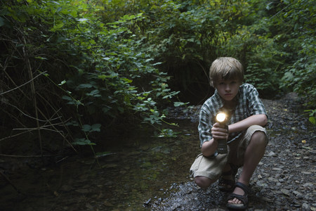 shadowed: Boy with torch by river LANG_EVOIMAGES