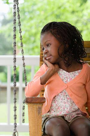 afro caribbean ethnicity: A girl sat on a swing seat LANG_EVOIMAGES
