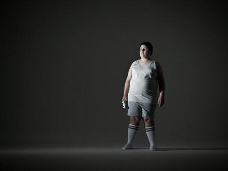 obesidad infantil: Muchacho que sostiene el regulador del juego video