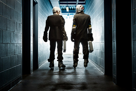 lit image: Two businessmen wearing ice hockey uniforms LANG_EVOIMAGES