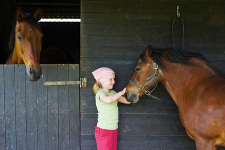 farmyards: A girl stroking a horse