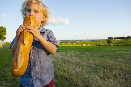 farmyards: A boy eating a baguette