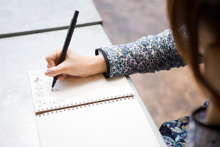 Woman drawing in notebook