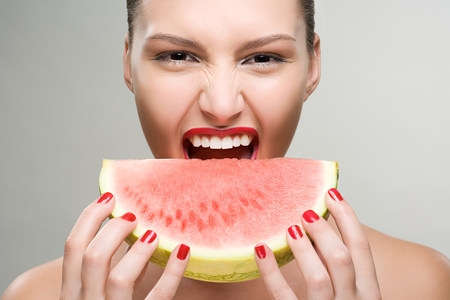 sliced watermelon: Young woman eating watermelon