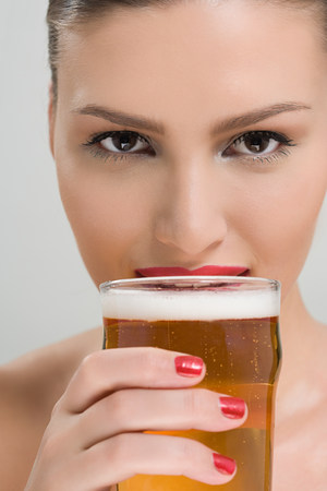 Woman drinking a pint of lager LANG_EVOIMAGES