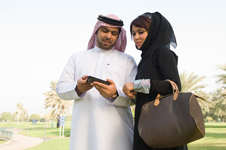 A young man showing his wife his cell phone LANG_EVOIMAGES
