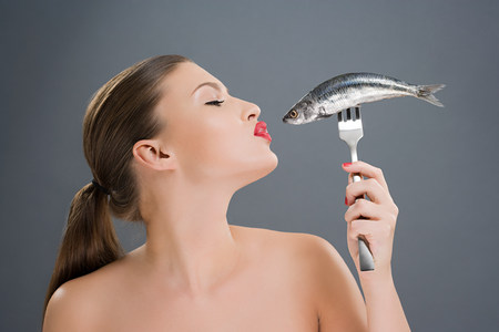 Woman kissing a fish on a fork