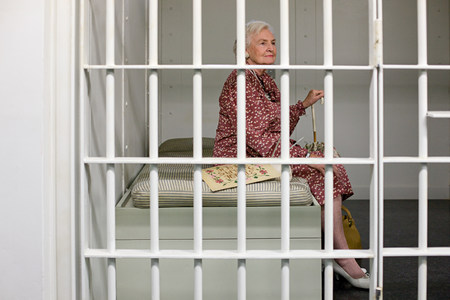 conscience: Senior woman in prison cell LANG_EVOIMAGES