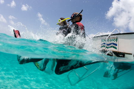 see through: Snorkelers jump into water. LANG_EVOIMAGES