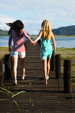 two persons only: Friends holding hands on jetty