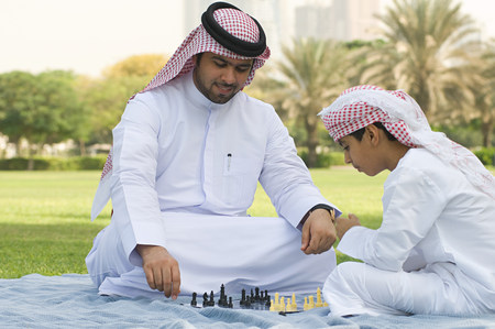 A father and son playing chess in a park LANG_EVOIMAGES