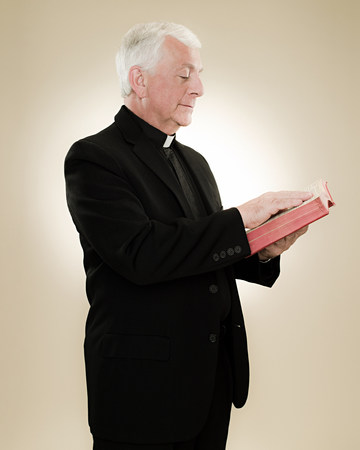 catholicism: A priest reading a bible LANG_EVOIMAGES