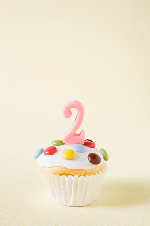 personas festejando: Cupcake with number two candle